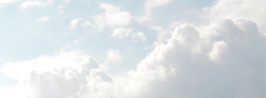 fluffy white clouds against a light blue sky