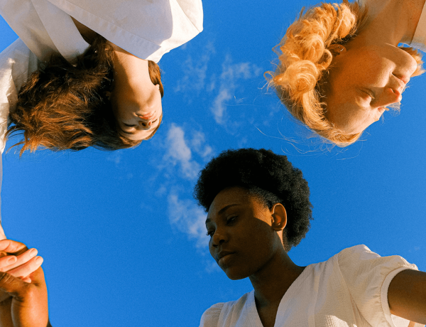 under a blue sky, 3 women holding hands in a circle