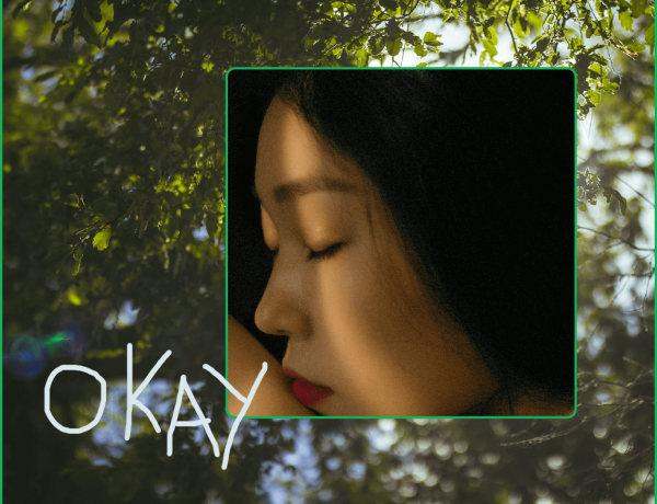 On a background of trees there is a close-up of a person's face, they have long dark hair and closed eyes, with the word 'okay' scrawled around them.