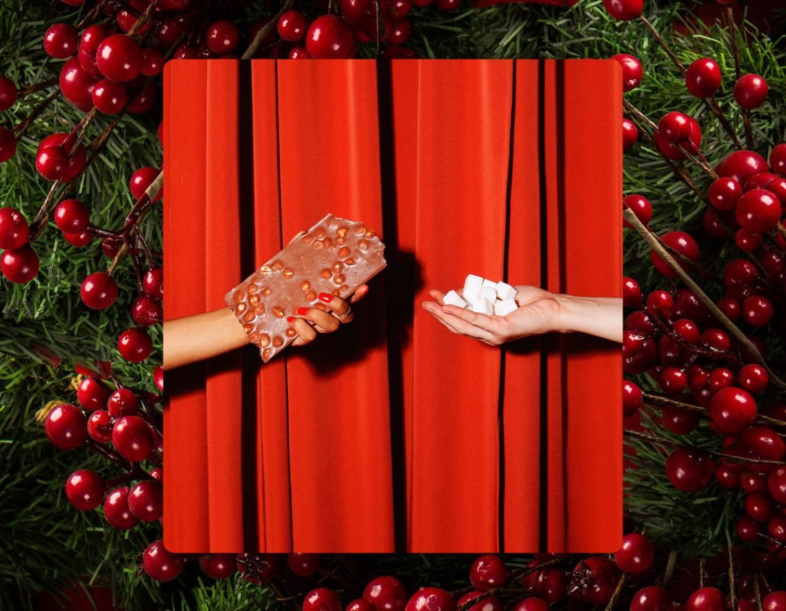 Two disembodied hands reach towards each other. One holds a chocolate bar; the other, a handful of sugar cubes. Behind the hands is a red stage curtain (closed) and the whole image is bordered by fir branches and burgundy berries