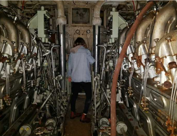 A woman with her back to the camera stands between walls of machinery and pipes.