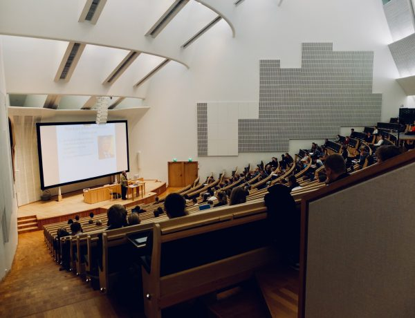 Photograph of a lecture hall, taken from the back of the room, with people sitting in the rows.