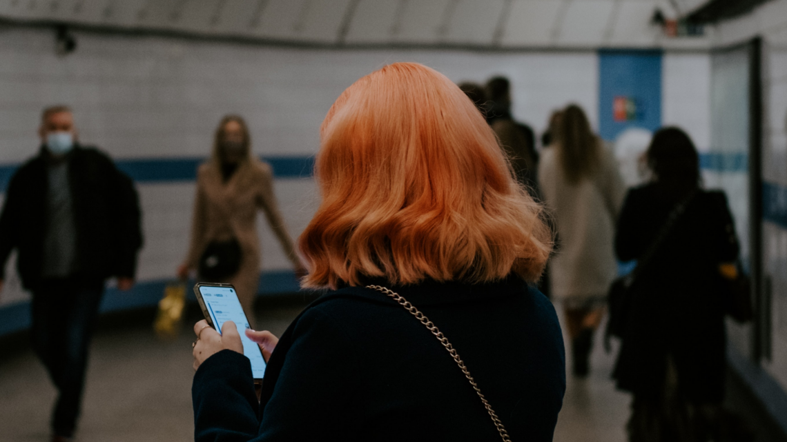 Photograph of a person using their phone while standing on a busy underground passageway. They have a short orange bob and are wearing a black coat, facing away from the camera.