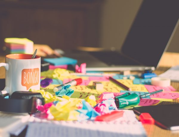 A messy desk covered in multicoloured sticky notes, a laptop and a mug