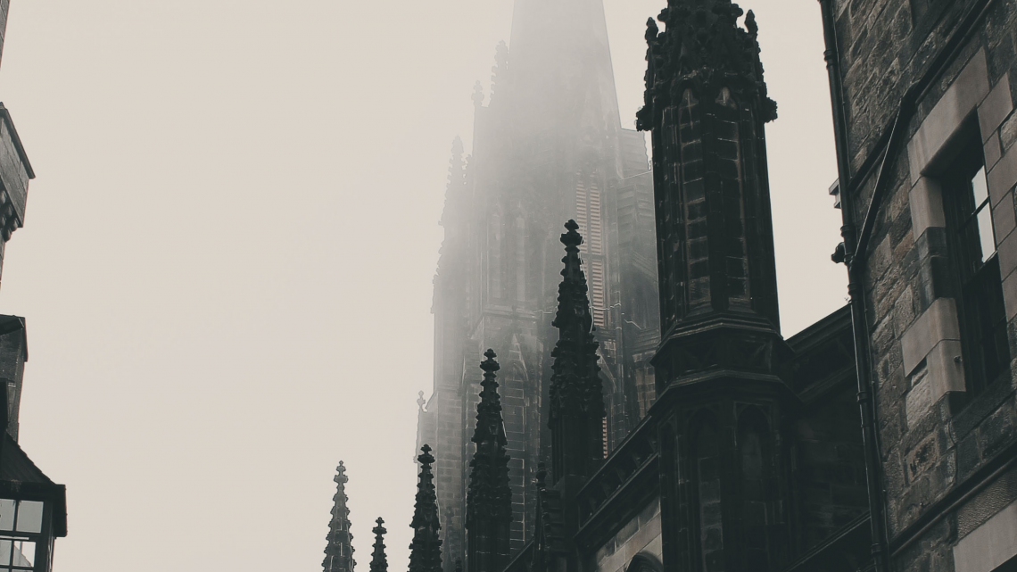 Photograph of a dark, gothic cathedral surrounded by a grey mist.